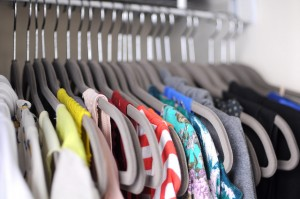 Organized closet with clothes on thin hangers.
