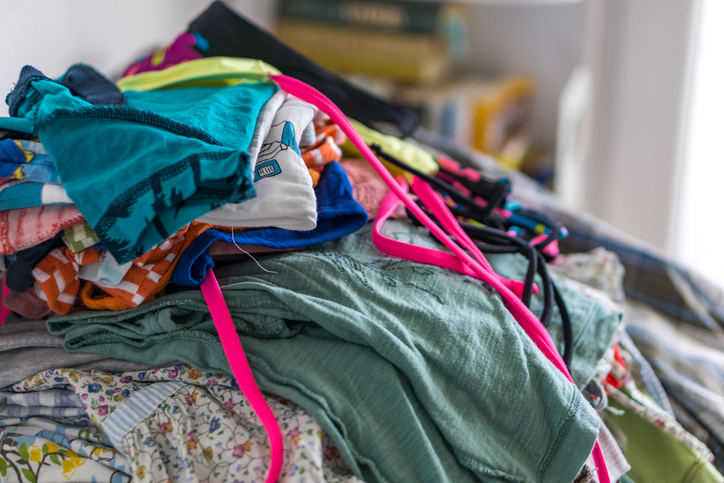 Pile of summer clothes on bed